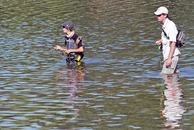 Loveland resident Trajan Barrett, left, and Nate Davis of Fort Collins fish together Wednesday afternoon in Lake Loveland near North Lake Park. Davis said they were using fly rods to fish for carp and that they had caught and released several of them.