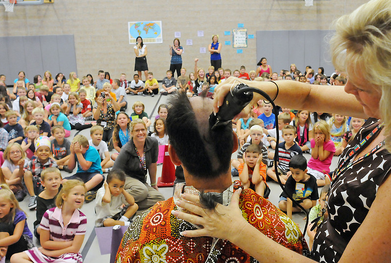Coyote Ridge Elementary School principal Diane Spearnack uses clippers to shave third grade teacher Dave Dellwardt's head during an assembly Thursday morning in the school's gymnasium. Dellwardt told his students last year that if more than 50 percent of them scored advanced on their CSAP tests he would reward them by having his head shaved. He honored his word after 66 percent of them scored advanced on the math portion of the test.