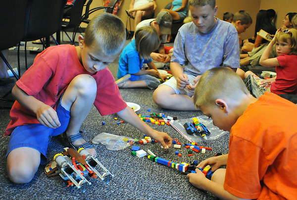 Josh O'Gorman, 9, left, Dakota Bowman, 11, Spencer Bowman, 9, and other youngsters use Lego blocks to make a variety of creations Saturday morning at the Loveland Public Library. The items created are on display at the library beginning today, but they'll eventually all be dismantled so the blocks can be used next month for another gettogether of young Lego enthusiasts.