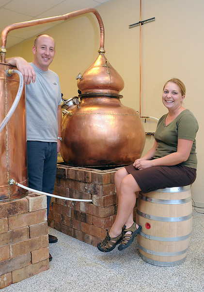 Kristian and Kimberly Naslund pose next to the pot still they use to make rum and other spirits at Dancing Pines Distillery, 1527 Taurus Court, No. 110, in Loveland.