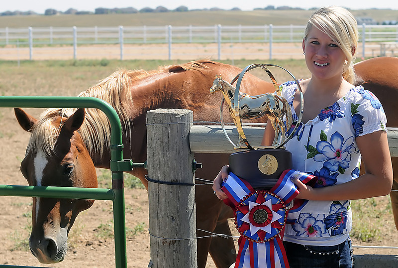 Alyssa Neiberger poses with one her horses named Banjo as she holds the championship trophy and sash she won at the American Quarter Horse Youth World show on Aug. 4 in Oklahoma City while riding on her horse named Credits for Heaven.