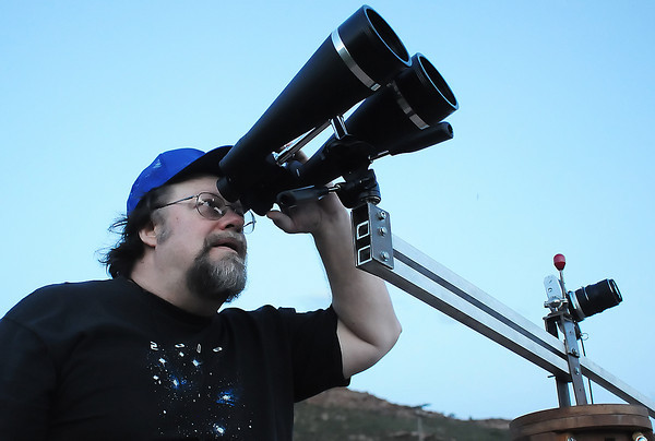 Northern Colorado Astronomical Society member Tom Teters of Fort Collins uses a pair of 20x90 binoculars to look at the moon and planets Thursday evening at the Bobcat Ridge Natural Area.