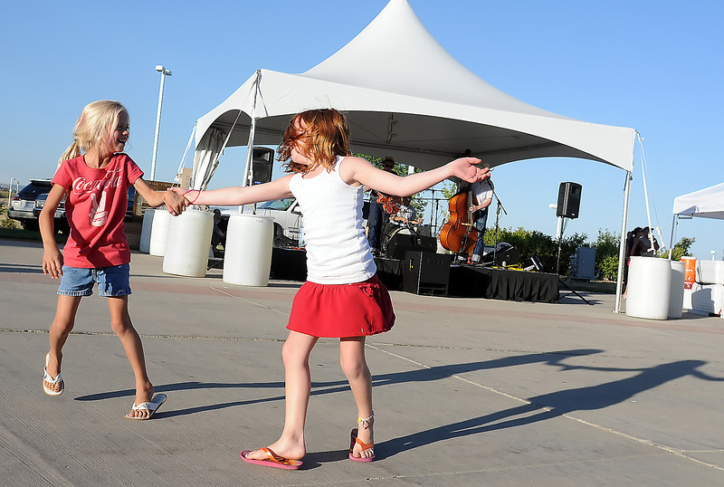 Avery Buhler, 7, of Fort Collins and Loveland resident Haylee Schaefer, 7, dance together while the band High Gear Daddies performs Friday during the Road Knights Car Show at The Ranch . The car show continues today from 8 a.m. to 10 p.m. and Sunday from 8 a.m. to 3 p.m.
