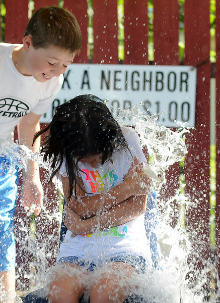 Seven-year-old Chloe Warner is drenched by water as Eli Solt, 11, left, looks on at the Soak a Neighbor booth during the Good Neighbor Festival on Sunday, Aug. 22, 2010 at First United Methodist Church, 533 N. Grant Ave.