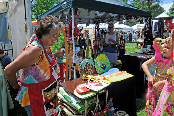 Virginia Stile, left, tries on one of the many aprons for sale at Eileen Maelzer's booth during Art in the Park at North Shore Park. Eileen and her friends were selling over 100 hand made quilts, aprons, flowers and other things.