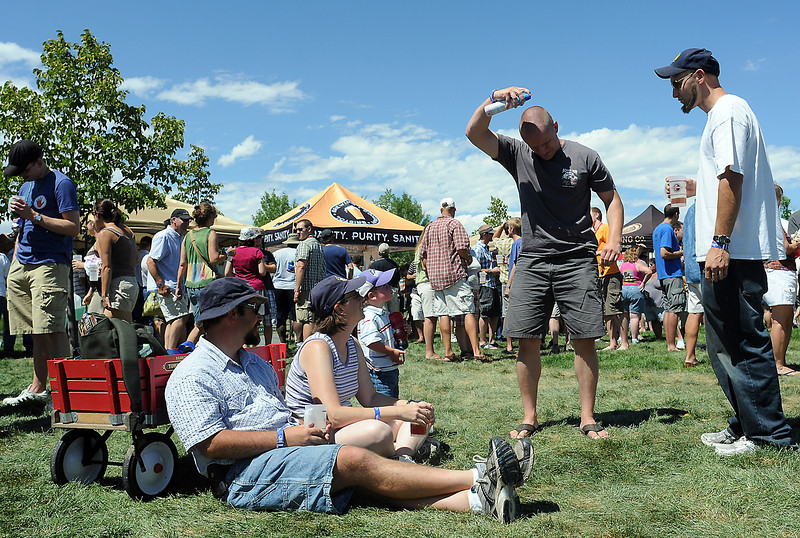 Jake Tilley, right, looks on while Daniel Carr applies some sunscreen he borrowed from Loveland residents, front to back from bottom, Carl Swanson, Shannon Swanson Koshiol and Tobin Swanson, 2, during the Gnarly Barley Brew Fest at The Ranch.