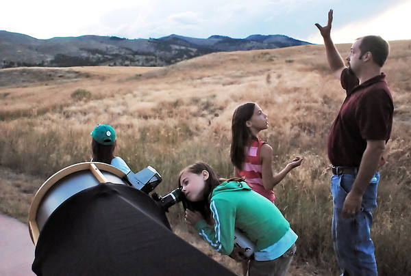 Members of the Domago family from Fort Collins use a telescope provided by the Northern Colorado Astronomical Society to look at the moon and planets Thursday evening at Bobcat Ridge Natural Area during an event to learn about and watch the Perseid meteor shower. From left are Chloe, 6, Georgia, 8, Sophia, 10, and Will.