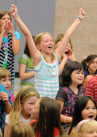 Coyote Ridge Elementary School fourth grader Reagan Jarnagin, 9, center, yells along with other students during an assembly Thursday morning as teacher Dave Dellwardt has his head shaved after saying he would do so if more than 50 percent of students in his third grade class scored advanced on last year's CSAP test.