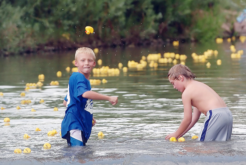 Loveland residents Kaden Butler, 8, left, and Jack Eberle, 8, play in the Big Thompson River as hundreds of rubber ducks float downstream after the first 100 winning ducks had been tallied for the Loveland Rotary Club's Duck Race on Saturday at Fairgrounds Park.