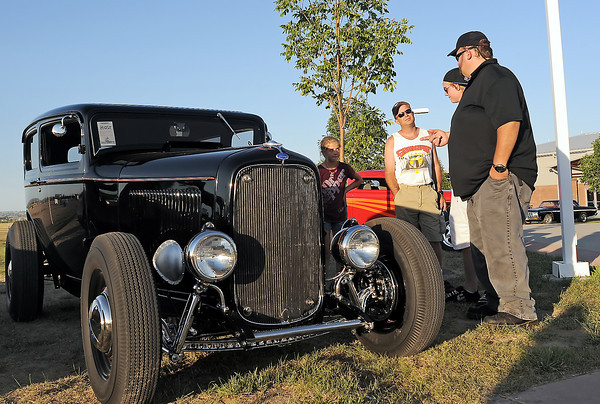 Scott Ahlquist, right, and his son, Greg, chat with Scott Buhler and his daughter, Shelby, 11, about Buhler's 1932 Ford sedan on display Friday at the Road Knights Car Show at The Ranch.