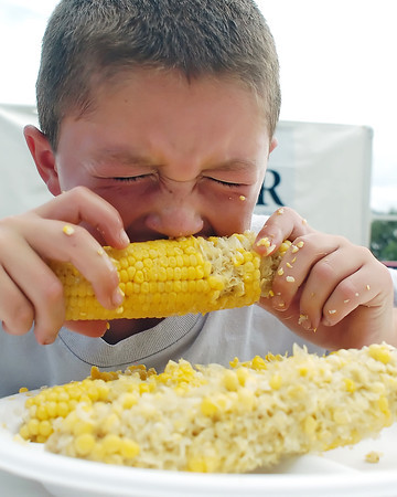 Aden Shaffer, 9, bites into an ear of corn during the corn eating contest Saturday as part of the Loveland Corn Roast Festival at Fairgrounds Park.
