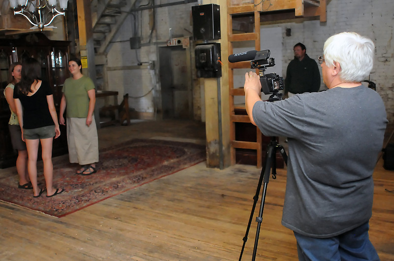 "Loveland resident Bill Chappell, right, prepares to shoot a scene for his documentary ""Three Legs Down"" on Saturday afternoon at the Loveland Feed and Grain building with actors, back from left to right, Celeste Guerrero, Nicole Hay, Heather Emig and Tac Doran."