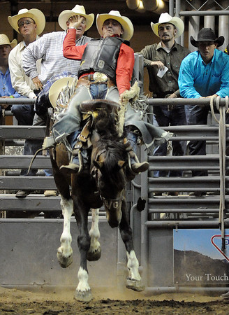 Jake Wright of Milford, Utah stays atop Falling Star on Monday night during the saddle bronc event of the Larimer County Fair and Rodeo at the Budweiser Events Center.