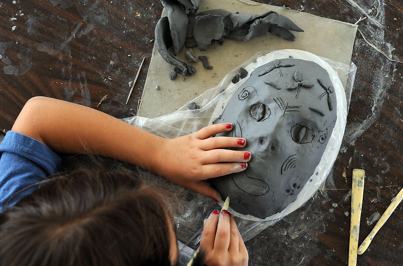 Zoanna Goar, 8, of Loveland creates a mask on Saturday during the Loveland Sculpture Invitational at Loveland High School. The tent was sponsored by the Thompson School District , Loveland Sculpture Group and Mile Hi Ceramics.
