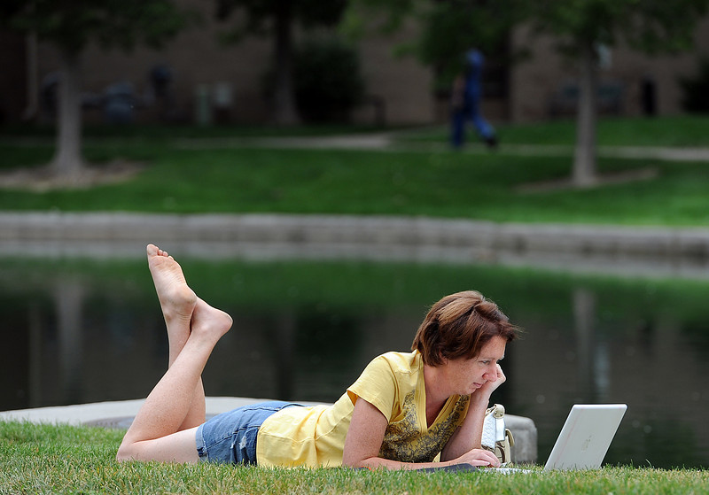 Cyndi Grafton of Loveland relaxes in the grass at Foote Lagoon Monday as she downloads music on her laptop.