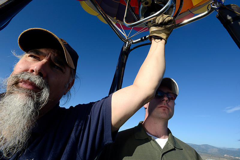 During his first time flying in a hot air balloon, Chris Meschuk, right, stands next to Pilot Jim Pansa, left, as they take in the sights from the sky above Loveland Friday.
