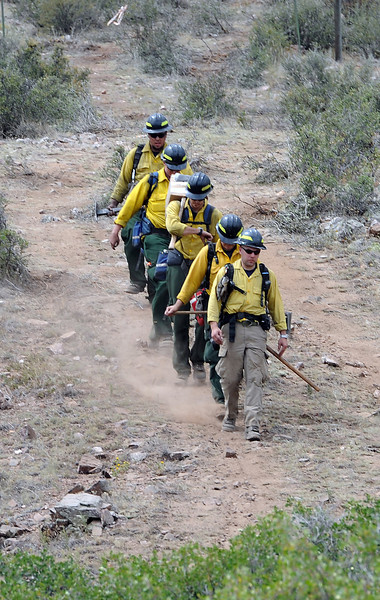 Larimer County Emergency Services Wildland Fire firefighters hike down after mopping up hot spots on two fires north of Flatiron Reservoir west of Loveland on Thursday.