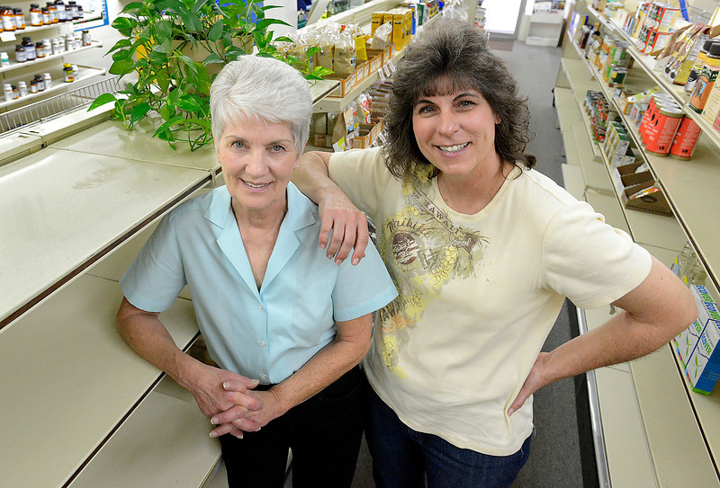 Jacki McAndrews, right, owner of Cabin Country Natural Foods, poses for a portrait with Kay Mjelde, left, the former owner and current employee, at the store Thursday in downtown Loveland. The store will be closing in a few weeks.