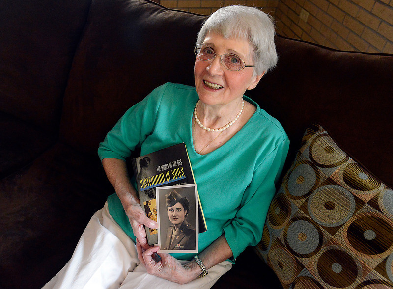 "Leonie Shannon, a World War II veteran who was a decoder during the war, poses Wednesday in her Loveland home holding a photo of her in her military uniform and a copy of ""Sisterhood of Spies,"" a book about the Office of Strategic Services, where she served."
