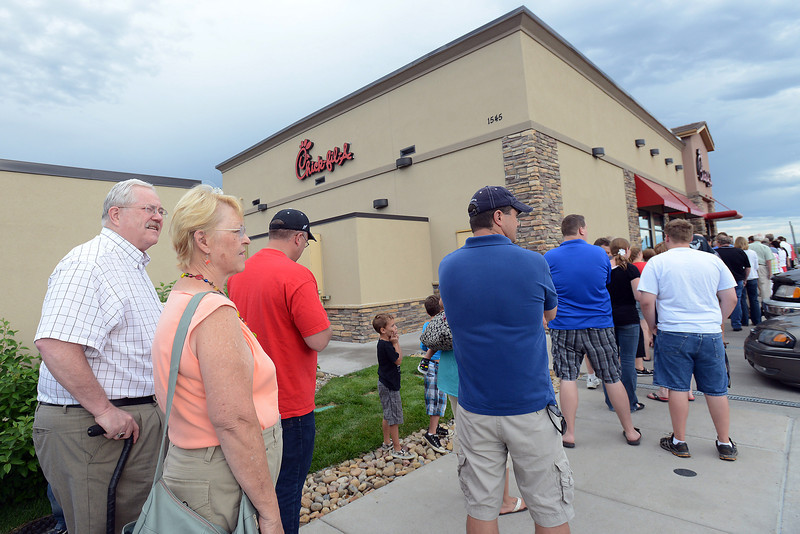 Greeley residents Jim and Lynda Beveridge, at left, stand in line outside the Chick-fil-A in Loveland on Wednesday evening during the dinner-time rush with others waiting to place their meal orders.