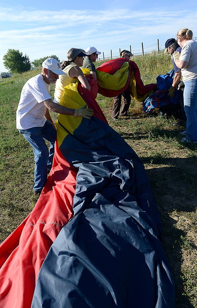 The 's Wonderful crew packs up the hot air balloon after a flight over Loveland Friday.