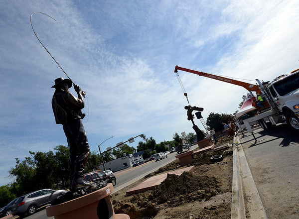 """After placing a bronze sculpture titled """"The Catch"""" by Mark Lundeen, left, crews work to install a George Lundeen sculpture titled """"Up For Grabs"""" Friday morning at Dairy Queen in downtown Loveland."""