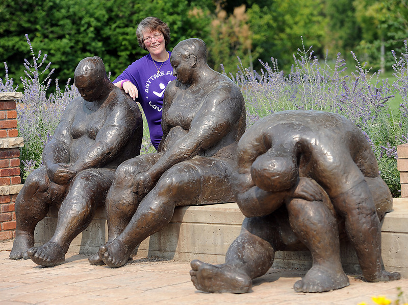 Susan Brock poses near a sculpture Tuesday at Benson Sculpture Garden Park in Loveland. The sculpture is sentimental to her given her weight loss story. She said before she lost weight she could relate to the sculpture, especially the figure with its head down, because she felt like she should keep her head down. She has inspired Anytime Fitness members with her weight loss. Now she is battling uterine cancer with no health insurance and there is a fundraiser for her.