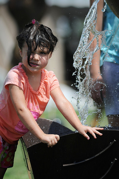 Josie Giovanni, 4, of Colorado Springs beats the heat in a sculpture fountain created by her father Mark Giovanni on Saturday during the Loveland Sculpture Invitational at Loveland High School.