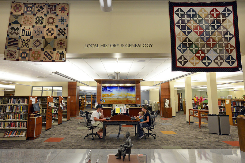 "Loveland residents Eric Solanyk, left, Meredith Solanyk, 1 1/2 and Stacey Solanyk use computers at the Loveland Public Library beneath several quilts on display in the galleria as part of the ""Civil War Era Quilts"" show."
