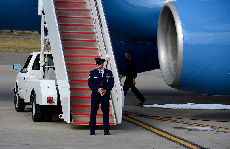 Secret Service and military personnel stand guard near Air Force One and check the tarmac Wednesday at the Fort Collins-Loveland Airport.