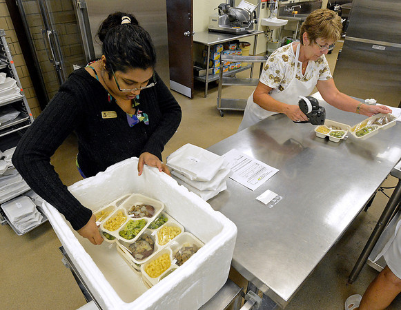 Meals on Wheels employee Jarita Webster, left, and volunteer Stevie Cissell pack meals into coolers Thursday before drivers deliver them in Loveland.