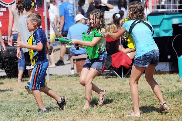 Olivia Veldhuizen, 11, right, and her sister Juliana Veldhuizen, 10, use water guns to squirt 9-year-old Jesse Dean while playing water tag at Loveland Laser Tag's booth at the Larimer County Fair on Saturday, Aug. 4, 2012 at The Ranch.