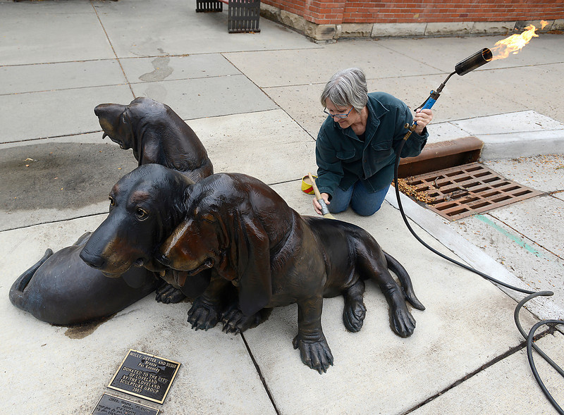 "After cleaning a bronze sculpture titled ""Molly, Deeter and Susie"" by artist Pat Kennedy, Debbie Bakel uses a torch and a brush to apply conservators wax to protect the sculpture from the elements Thursday at the corner of Cleveland Avenue and Fifth Street in Loveland."
