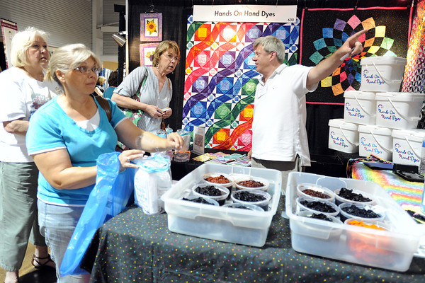 Karen McGregor, left, Carol Newby and Gail Eamon purchase fabric dye kits from David Sherwood at his Hands On Hand Dyes booth during the Rocky Mountain Quilt Festival on Saturday, Aug. 198, 2012 at The Ranch. The festival continues today from classes quilting classes starting at 9 a.m. and vendor booths open from 10 a.m. to 4 p.m.