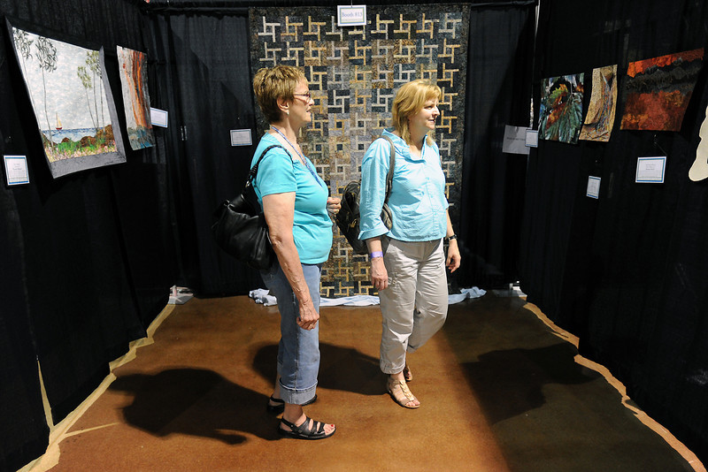 Colorado Springs residents Mauna Proctor, left, and Jane Butcher looks at quilts on display during the Rocky Mountain Quilt Festival on Saturday, Aug. 18, 2012 at The Ranch.