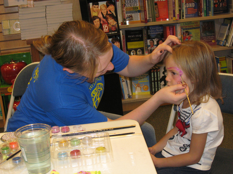 20rhadic~1.jpg Big Thompson Interact Club member Dyrani Clark, left, works the face painting area of the Loveland Rotary Dictionary Book Fair Sunday, painting a flower on Ava Gintoli's face.