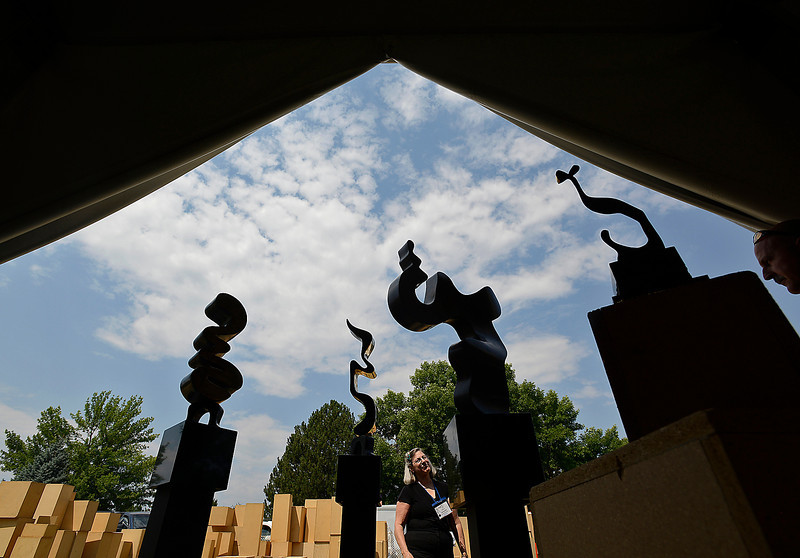 Artist Joyce Steinfeld of Los Gatos, California, center, checks to make sure her bronze sculptures are level Thursday while setting up her space in preparation for this weekend's Sculpture in the Park at Benson Benson Park Sculpture Garden in Loveland. Volunteer Mark Moore, far right, helps her with the sculptures.