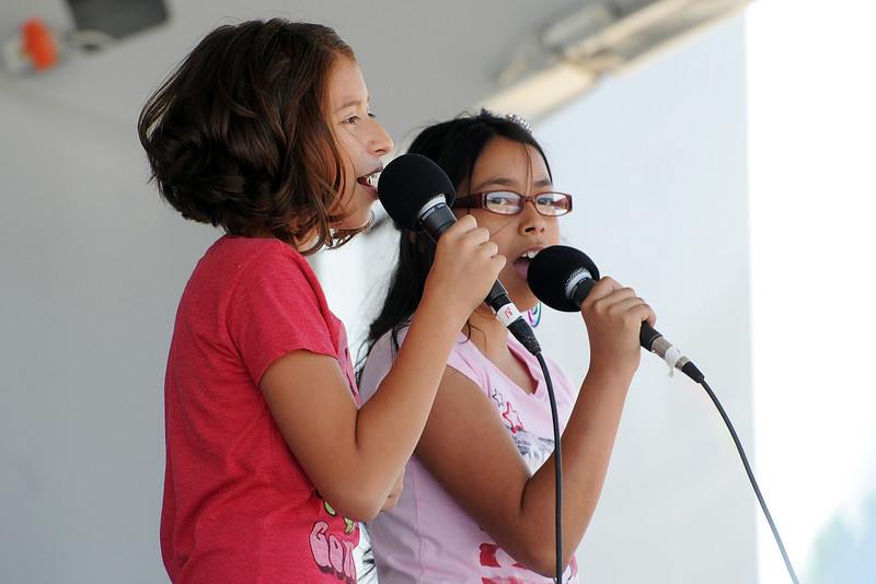 Greeley residents Alexis Hernandez, 11, left, and Alexis Rodriguez, 11, sing a song together during a break in competition for Loveland's Got Talent on Saturday, Aug. 25, 2012 at Fairgrounds Park.