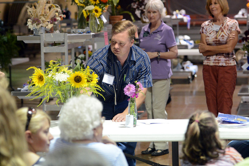 Spectators look on while open class flowers judge Curtis Utley, middle, examines and ranks some entries during the Larimer County Fair on Thursday, Aug. 2, 2012 at The Ranch.