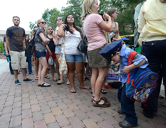 James Green of Estes Park, 4, looks for a place to hang the handcuffs on his police costume as he waits in line with his sister and Grandfather Tuesday to hear President Obama speak at CSU in Fort Collins.