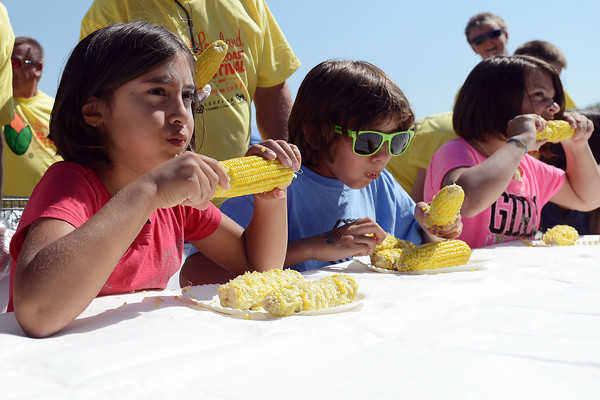 "Emma Duran, 9, left, Roman Waldman, 11 and Adisyn Nyhart, 9, compete in the corn eating contest during the Old Fashioned Corn Roast Festival on Saturday, Aug. 25, 2012 at Fairgrounds Park. Roman won his age group and afterward said, ""I just chomped it down going in spirals."""