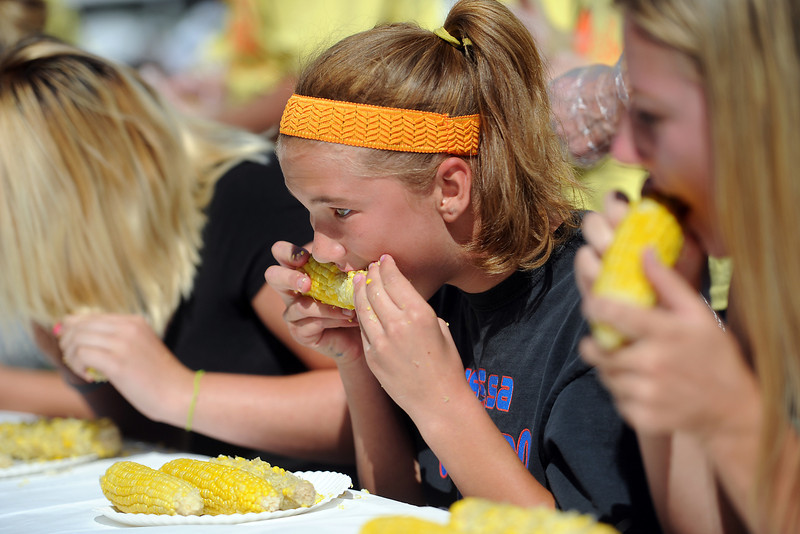 Jennifer Barnhart, 15, middle, competes with others in the Old Fashioned Corn Roast corn eating contest on Saturday, Aug. 25, 2012 at Fairgrounds Park.