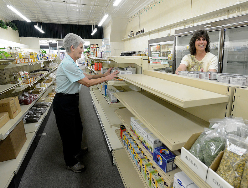Kay Mjelde, left, employee and former owner of Cabin Country Natural Foods, and owner Jacki McAndrews, right, move merchandise and take down some shelves Thursday at the downtown Loveland store that will be closing in a few weeks.