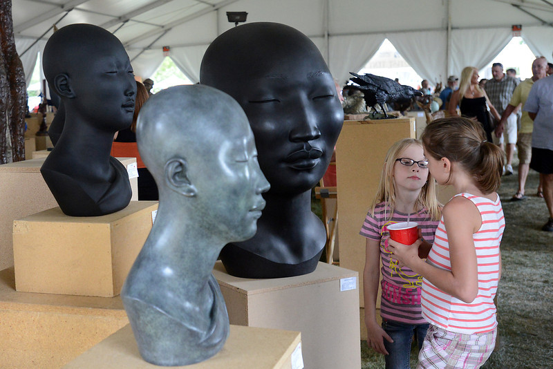 Longmont residents Sarah Seybold, 12, right, and her sister Skyler Seybold, 8, look at sculptures by Erie-based artist Scarlett Kanistanaux while attending Sculpture in the Park on Saturday, Aug. 11, 2012 at the Benson Sculpture Garden.