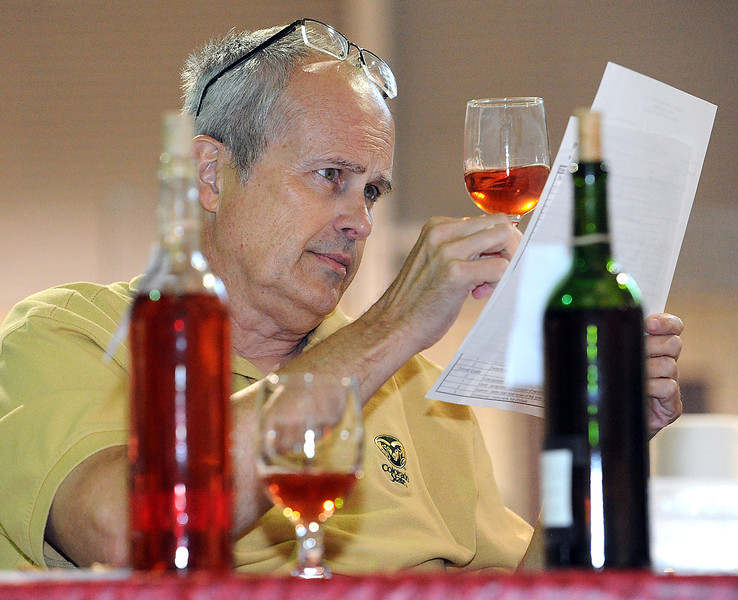 Jeff Miller inspects the color of a blush wine Wednesday while judging wine and liqour during the Larimer County Fair at The Ranch.