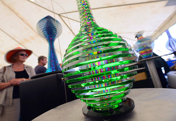 Janet Tobin takes a closer look at cold fusion glass sculptures by artists Mark and Julie Glocke Friday during the Loveland Sculpture Invitational in Loveland.
