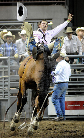 Tyler Scales of Severance hangs on to a horse named Conviction during the bareback riding event Monday night during the Larimer County Fair and Rodeo at the Budweiser Events Center.