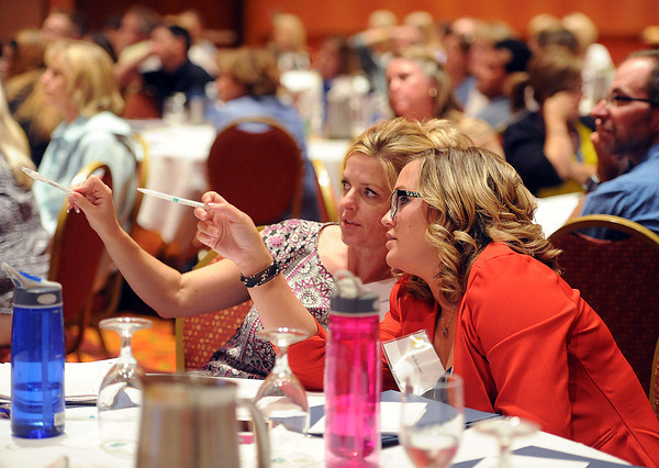 Jennifer Brownhill, left, assistant principal at Mountain View High, and Karla Quinones, right, english and theater teacher at Mountain View, recieve training with about 200 Thompson School District employees on Colorado's new principal and teacher evaluation law Monday at Embassy Suites in Loveland.