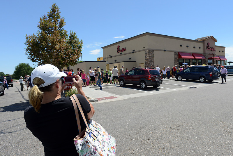 Natalie Morgan uses her cell phone to take photos of the line outside the Loveland Chick-fil-A restaurant as a throng of customers waits to place their orders during lunchtime Wednesday, Aug. 1, 2012. Former Arkansas Gov. Mike Huckabee declared Aug. 1 Chick-fil-A Appreciation Day on his Facebook page and encouraged people to patronize the business.
