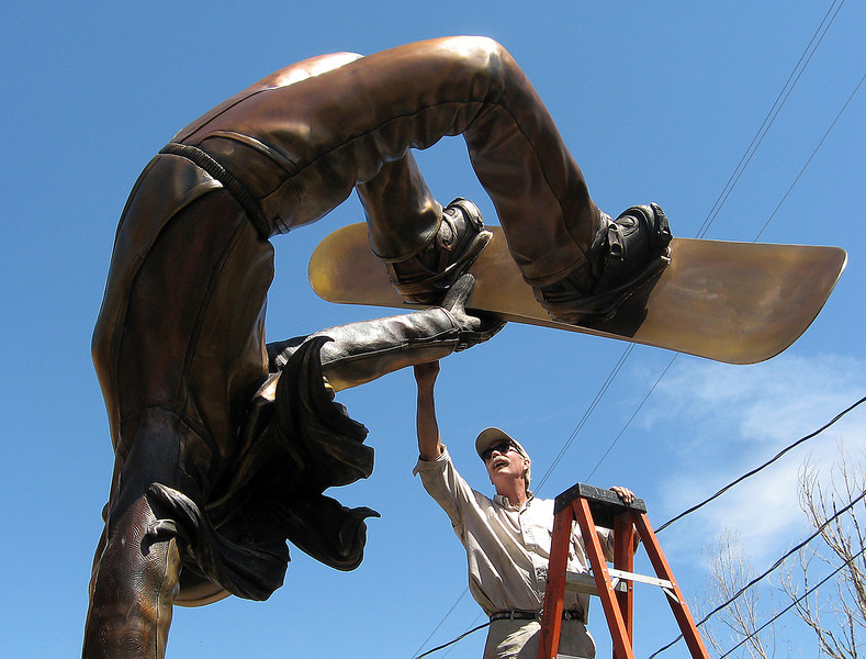 "George Lundeen works on the final patina of a sculpture, ""Up for Grabs,"" that is part of a series destined for a Utah sporting goods company."